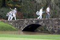 Lee Westwood, left, and Matt Kuchar cross over Nelson's Bridge after their tee shots on the 13th hole during the first round of the Masters golf tournament Thursday, Nov. 12, 2020, in Augusta, Ga. (Curtis Compton/Atlanta Journal-Constitution via AP)