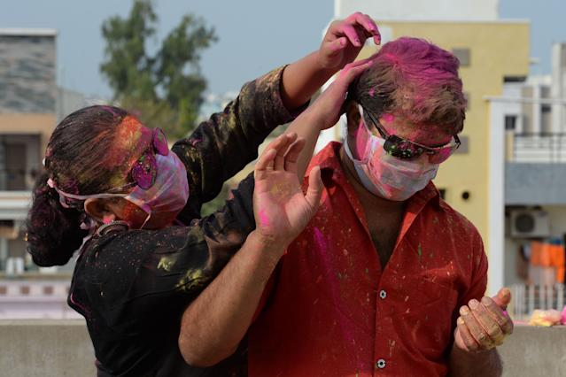 A couple wearing facemasks as a preventive measure against the COVID-19 coronavirus, apply smear their faces with coloured powder during a friends gathering the celebrate 'Holi', the Hindu spring festival of colours, in Hyderabad on March 8, 2020. - Holi, the popular Hindu spring festival of colours is observed in India and across countries at the end of the winter season on the last full moon of the lunar month. (Photo by NOAH SEELAM / AFP) (Photo by NOAH SEELAM/AFP via Getty Images)