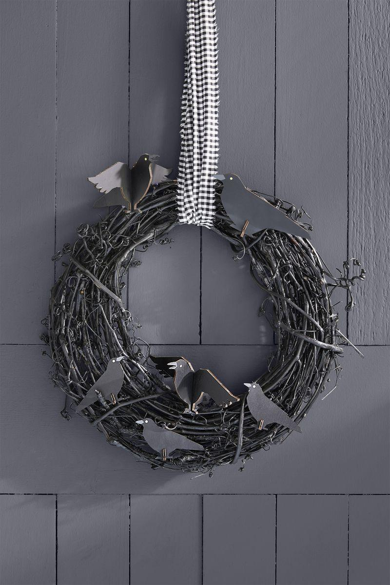 <p>This Halloween-inspired wreath may be a little spooky for the start of the season, but it's bound to make your home the talk of the town come October. </p><p><strong>Make the wreath: </strong>Start with a grapevine wreath and spray-paint it black. Next, use black wire to secure cardboard crows and hang with gingham ribbon. </p>