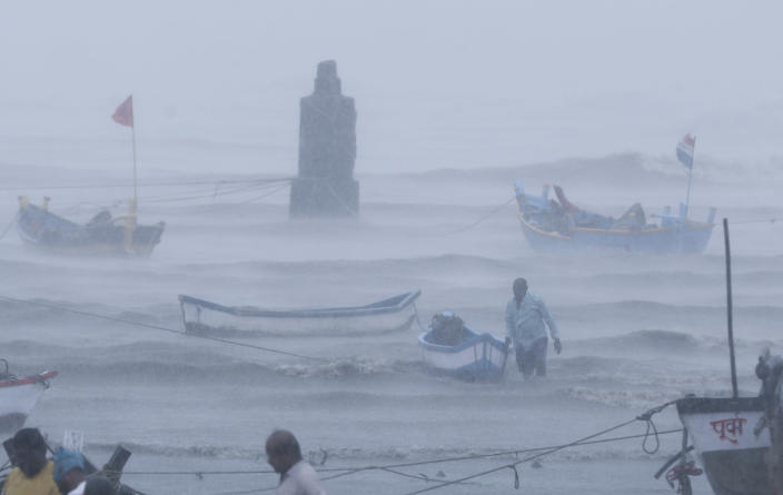 A fisherman waits for help as he tries to move a fishing boat to a safer ground on the Arabian Sea coast in Mumbai, India, Monday, May 17, 2021. Cyclone Tauktae, roaring in the Arabian Sea was moving toward India's western coast on Monday as authorities tried to evacuate hundreds of thousands of people and suspended COVID-19 vaccinations in one state. (AP Photo/Rafiq Maqbool)