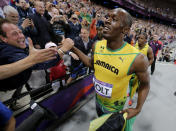 Jamaica's Usain Bolt celebrates winning gold in the men's 100-meter final, followed by silver medalist Yohan Blake of Jamaica, back right, during the athletics in the Olympic Stadium at the 2012 Summer Olympics, London, Sunday, Aug. 5, 2012. (AP Photo/David J. Phillip )