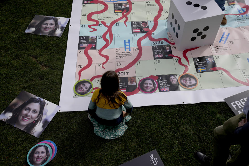 """Gabriella, the seven year old daughter of imprisoned British-Iranian Nazanin Zaghari-Ratcliffe joins in a game on a giant snakes and ladders board in Parliament Square, London, to show the """"ups and downs"""" of Zaghari-Ratcliffe's case to mark the 2,000 days she has been detained in Iran, Thursday, Sept. 23, 2021. Zaghari-Ratcliffe was originally sentenced to five years in prison after being convicted of plotting the overthrow of Iran's government, a charge that she, her supporters and rights groups deny. While employed at the Thomson Reuters Foundation, the charitable arm of the news agency, she was taken into custody at the Tehran airport in April 2016 as she was returning home to Britain after visiting family. (AP Photo/Matt Dunham)"""