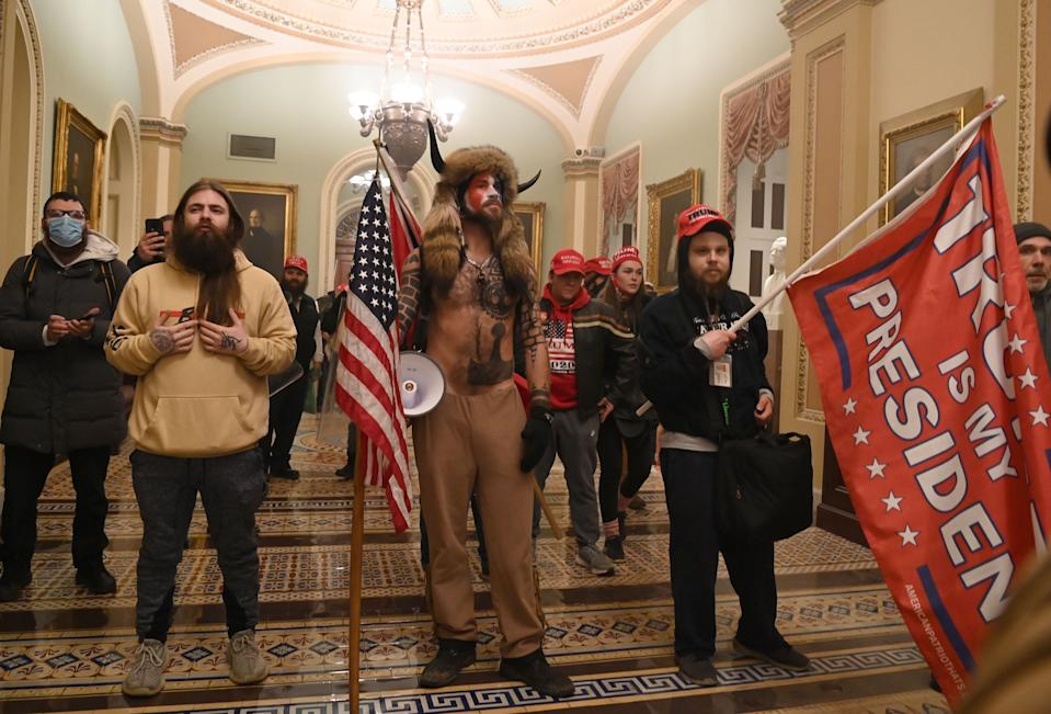 Supporters of US President Donald Trump, including member of the QAnon conspiracy group Jake Angeli, aka Yellowstone Wolf (C), enter the US Capitol on January 6, 2021, in Washington, DC. - Demonstrators breeched security and entered the Capitol as Congress debated the a 2020 presidential election Electoral Vote Certification.