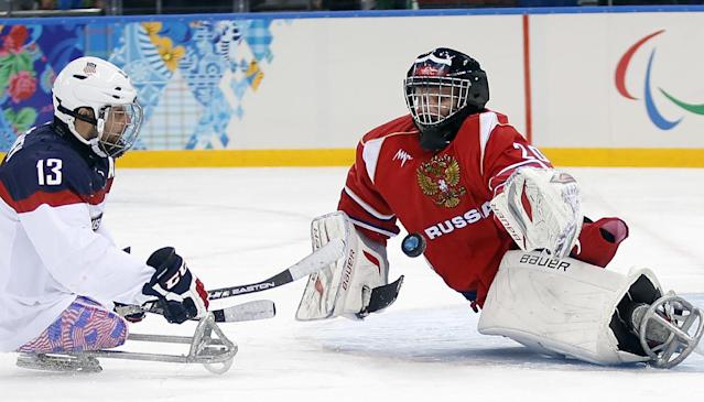 United States's Joshua Sweeney, left, shots on goal as Russia's Vladimir Kamantcev, right, try to defend during the gold medal ice sledge hockey match between United States and Russia at the 2014 Winter Paralympics in Sochi, Russia, Saturday, March 15, 2014. (AP Photo/Pavel Golovkin)