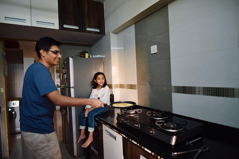 Father cooking while daughter waits on the kitchen counter