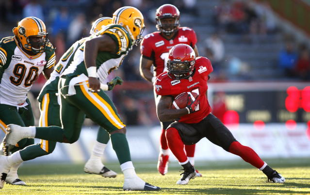 Edmonton Eskimos' Lee Robinson, centre, and Almondo Sewll close in on Calgary Stampeders' LaMarcus Coker during first half CFL pre-season football action in Calgary, Alta., Friday, June 15, 2012. THE CANADIAN PRESS/Jeff McIntosh