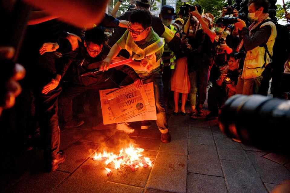 """<div class=""""inline-image__caption""""><p>People burn a Chinese national flag in central Taipei on October 25, 2020 at the end of a march in support of Save12, the campaign to save twelve Hong Kong pro-democracy activists who on August 23 were caught by mainland Chinese authorities trying to flee Hong Kong to Taiwan.</p></div> <div class=""""inline-image__credit"""">Photo by CHRIS STOWERS/AFP via Getty Images</div>"""