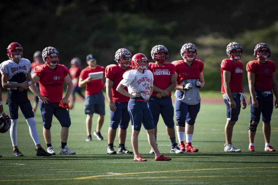 Simon Fraser University football team kicker Kristie Elliott, center, stands on the field with teammates during practice in Burnaby, B.C., Tuesday, Sept. 21, 2021. Elliott is enjoying her milestone in college football. Earlier this month, she became the first Canadian woman to play in an NCAA football game. (Darryl Dyck/The Canadian Press via AP)