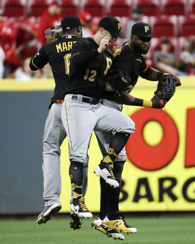 Pittsburgh Pirates center fielder Starling Marte, left, left fielder Corey Dickerson (12) and right fielder Gregory Polanco, right, celebrate after closing the ninth inning of a baseball game against the Cincinnati Reds, Saturday, July 21, 2018, in Cincinnati. (AP Photo/John Minchillo)