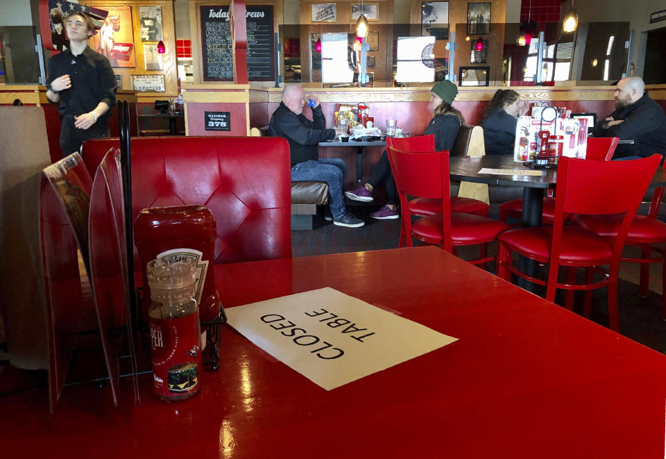 """FILE - In this March 15, 2020, file photo, a Red Robin restaurant in Tigard, Ore., has closed some tables in order to maintain social distancing between diners per CDC guidelines. Oregon Gov. Kate Brown on Friday, Nov. 13, 2020, announced a statewide two-week """"freeze"""" which will limit restaurants and bars to take-out only and close gyms, indoor and outdoor recreational facilities during that period. If people do not abide by the governor's latest mandates, which restricts social gatherings to six people, they could face a citation, fine or arrest. (AP Photo/Gillian Flaccus, File)"""