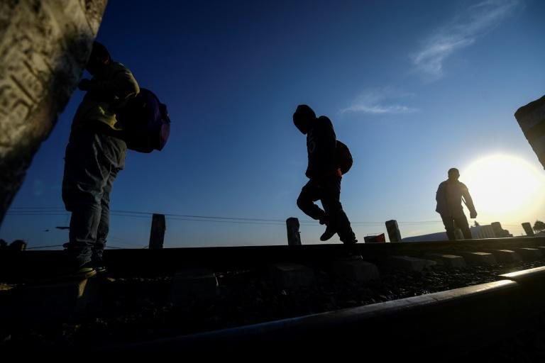 Central American migrants walk on rail tracks in the Mexican state of Tlaxcala on their way to seek safety in the United States in April 2021