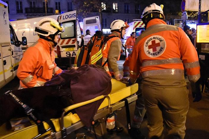 Rescue workers evacuate an injured person near the Bataclan concert hall in central Paris, on November 13, 2015 (AFP Photo/Dominique Faget)