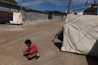 A boy plays next to a newly built concrete wall inside the Ritsona camp for refugees and migrants