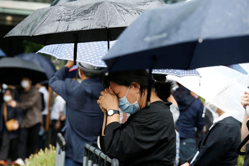 A woman mourns as the hearse carrying late Seoul Mayor Park Won-soon leaves Seoul City Hall Plaza after his funeral, in Seoul