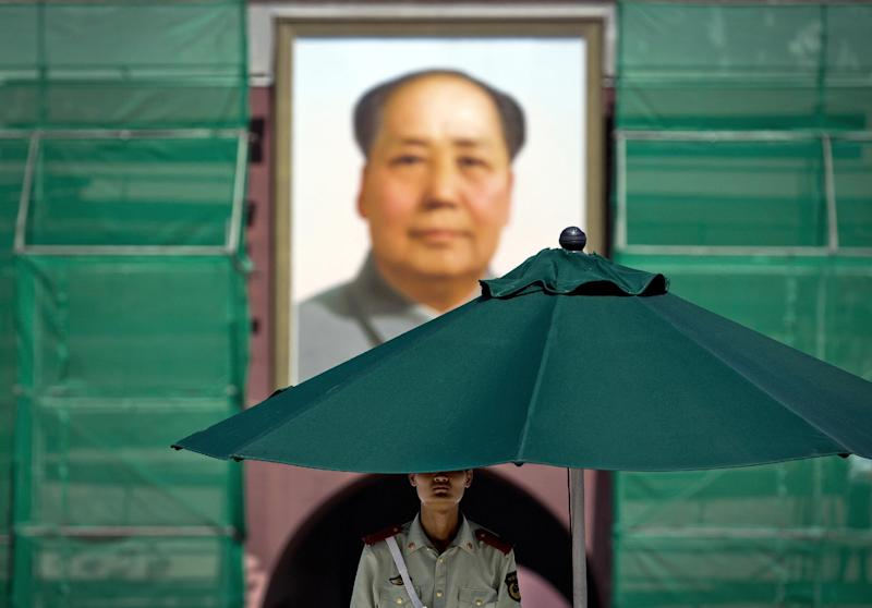 A Chinese paramilitary policeman stands guard under an umbrella against a portrait of Communist leader Mao Zedong at Tiananmen Gate in Beijing Wednesday, Sept. 5, 2012. Talks between U.S. Secretary of State Hillary Rodham Clinton and Chinese leaders Wednesday failed to narrow gaps on how to end the crisis in Syria and how to resolve Beijing's territorial disputes with its smaller neighbors over the South China Sea. (AP Photo/Andy Wong)