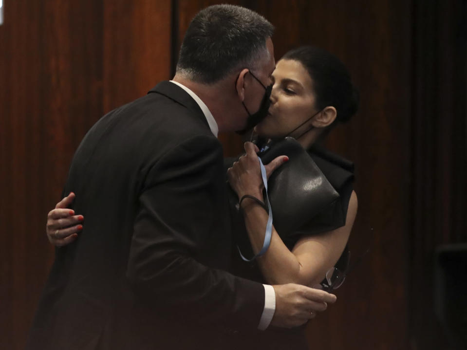 Israeli politician Gideon Saar of the New Hope party kisses his wife Geula Even-Saar during a Knesset session in Jerusalem Sunday, June 13, 2021. Naftali Bennett is expected later Sunday to be sworn in as the country's new prime minister, ending Prime Minister Benjamin Netanyahu's 12-year rule. (AP Photo/Ariel Schalit)