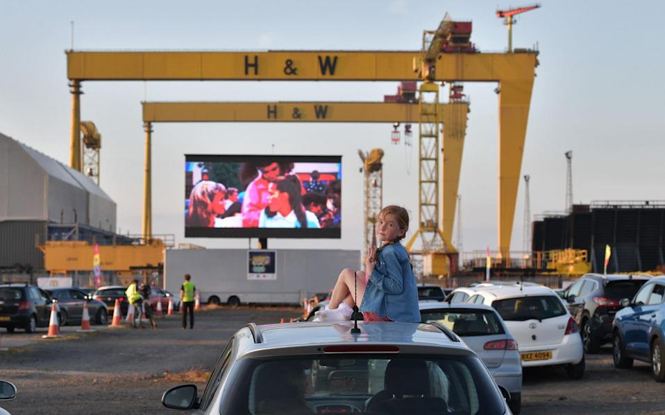 Bridget Nolan watches Grease on the big screen from the roof of her mothers car in the Titanic Quarter beneath the famous Harland and Wolff cranes on June 13, 2020 in Belfast, Northern Ireland. The drive-in cinema is the first of its kind taking place in the UK as some of the restrictions surrounding the Covid-19 pandemic are relaxed. - Getty Images