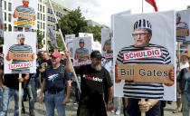 """People attend a protest rally in Berlin, Germany, Saturday, Aug. 29, 2020 against new coronavirus restrictions in Germany, holding a sign with Bill Gates in prison clothes, reading """"Guilty"""". Police in Berlin have requested thousands of reinforcements from other parts of Germany to cope with planned protests at the weekend by people opposed to coronavirus restrictions. (AP Photo/Michael Sohn)"""
