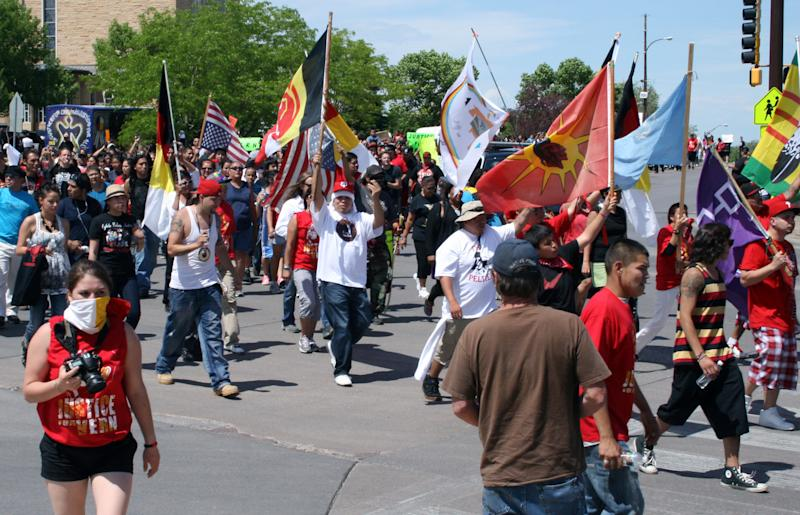 Hundreds of people march more than two miles from Memorial Plaza in Rapid City, S.D., to Rapid City Regional Hospital on Monday, May 21, 2012. The march, organized by American Indian Movement founder Dennis Banks, was in support of a man who says the letters KKK were carved into his stomach while undergoing surgery at the hospital. (AP Photo/Kristi Eaton)
