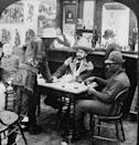 <p>A man in a fringed leather jacket and cowboy hat holds a revolver as he argues with a fellow gambler in a bar room dispute scene during the Klondike Gold Rush in Alaska. <br></p>
