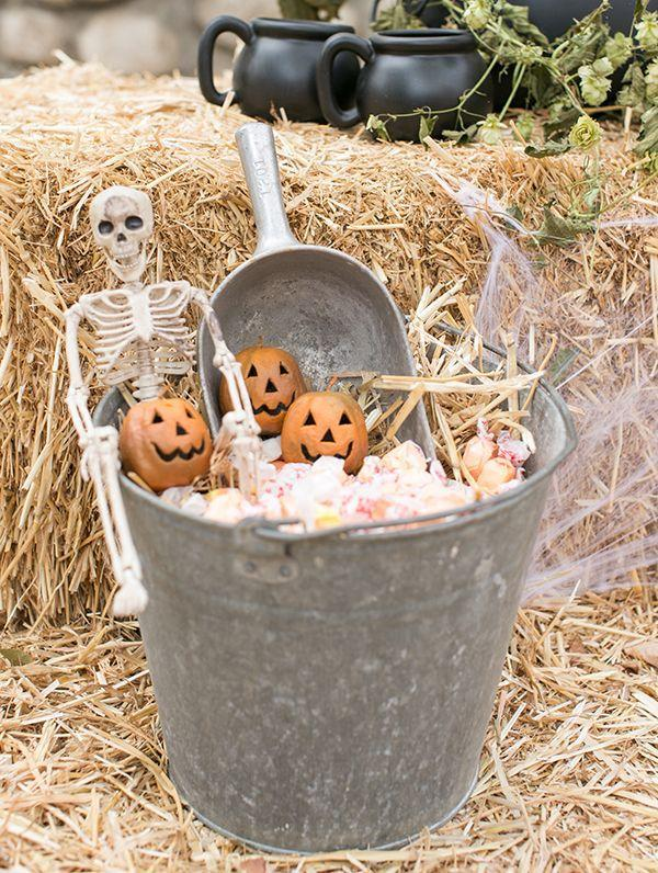 "<p>If you aren't going to be home (or don't want to answer the door) on Halloween night, fill a pail up with candy and put on top a bale of hay. Add a skeleton and some pumpkins and you're ready for trick-or-treaters!</p><p>See more at <a href=""https://sugarandcharm.com/2017/10/a-charming-and-traditional-halloween-party.html?section-36"" rel=""nofollow noopener"" target=""_blank"" data-ylk=""slk:Sugar and Charm"" class=""link rapid-noclick-resp"">Sugar and Charm</a>.</p>"
