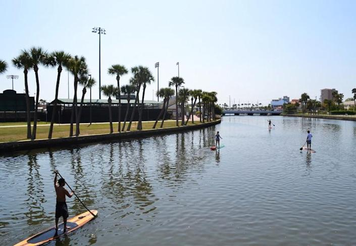 This March 22, 2011 photo provided by Three Brothers Boards shows Austin Marvin and tour customers passing the Jackie Robinson Memorial Ball Park on the Halifax River, Daytona Beach, Fla. A sort of combination between surfing and kayaking, standup paddling has exploded in popularity the past few years. It's relatively easy and can be done just about anywhere there's water. (AP Photo/Three Brothers Boards, Justin Murray)