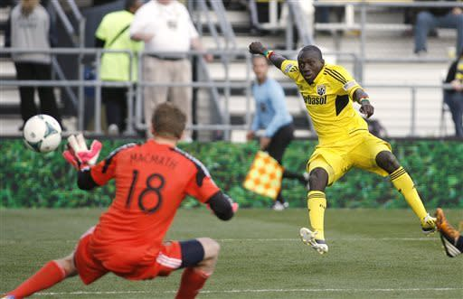 Columbus Crew's Dominic Oduro, right, scores against Philadelphia Union goalie Zac MacMath during the second half of an MLS soccer game in Columbus, Ohio, Saturday, April 6, 2013. The game ended in a 1-1 tie. (AP Photo /Mike Munden)