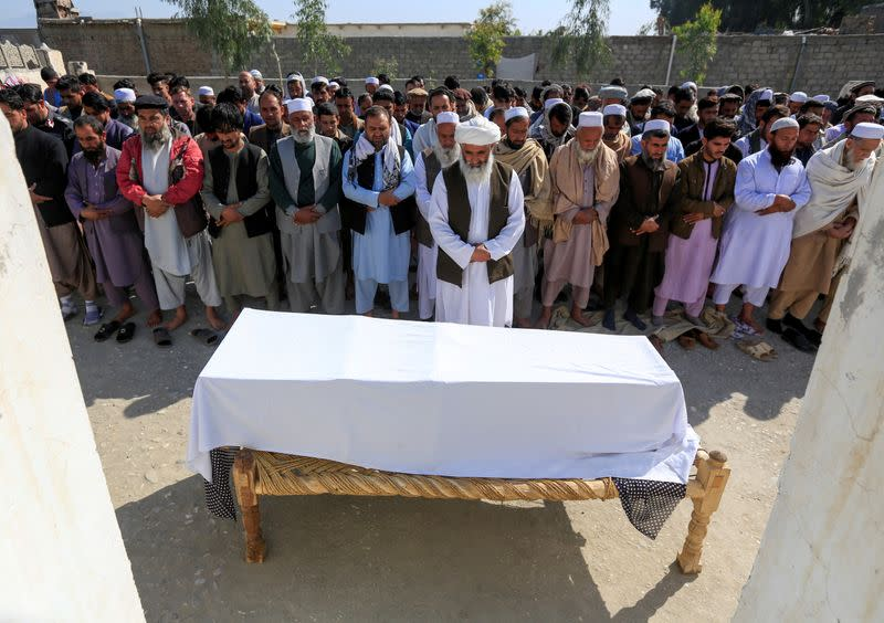 FILE PHOTO: Afghan men pray in front of the coffin of one of three female media workers who were shot and killed by unknown gunmen, in Jalalabad