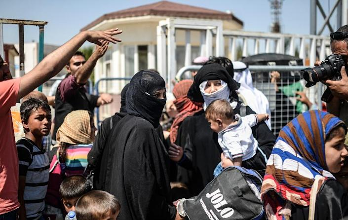 Syrian refugees wait at the Akcakale border crossing in Turkey before returning to northern Syrian town of Tal Abyad, on June 17, 2015 (AFP Photo/Bukent Kilic)