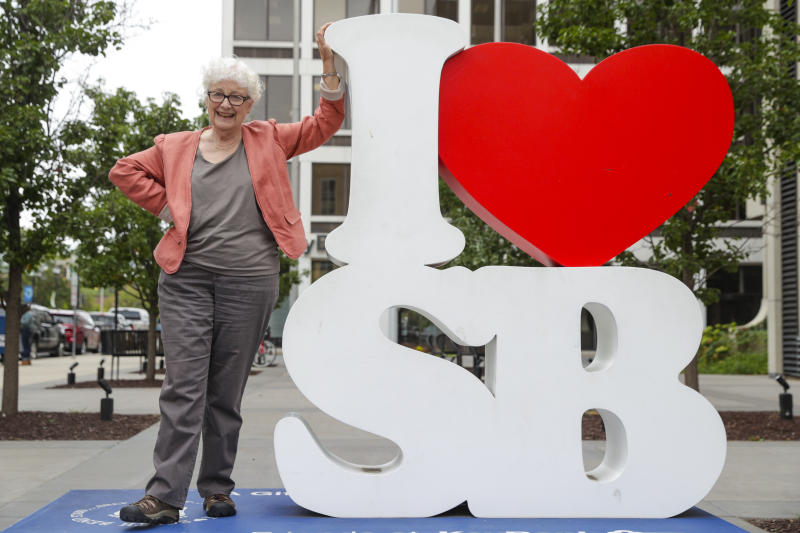 """Anne Montgomery, mother of Democratic presidential candidate South Bend Mayor Pete Buttigieg, poses on an """"I Love South Bend"""" statue outside his campaign office in South Bend, Ind., Wednesday, Sept. 25, 2019. (AP Photo/Michael Conroy)"""