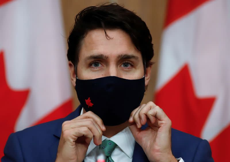 FILE PHOTO: Canadian Prime Minister Justin Trudeau puts on a mask at a news conference in Ottawa
