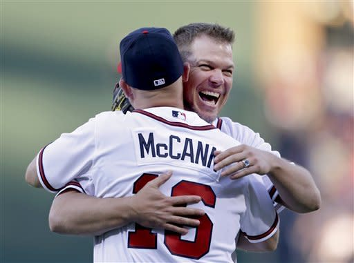 Former Atlanta Braves first baseman Chipper Jones, left, hugs Braves catcher Brian McCann after throwing out the first pitch for an opening day baseball game between the Braves and the Philadelphia Phillies, Monday, April 1, 2013, in Atlanta. (AP Photo/David Goldman)