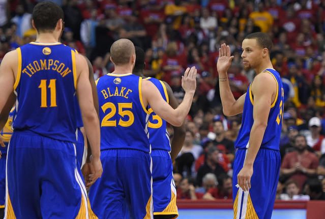 Golden State Warriors guard Stephen Curry, right, congratulates Steve Blake, center, as Klay Thompson looks on during a timeout in the second half in Game 1 of an opening-round NBA basketball playoff series, Saturday, April 19, 2014, in Los Angeles. The Warriors won 109-105. (AP Photo/Mark J. Terrill)