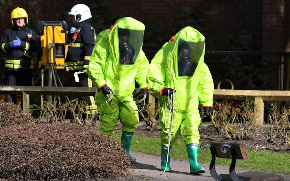 Members of the emergency services in green biohazard encapsulated suits arrive to afix the tent over the bench where Sergei and Yulia Skripal were found on March 4, 2018, in a critical condition at The Maltings shopping centre in Salisbury. Photo taken March 8, 2018. - BEN STANSALL/AFP