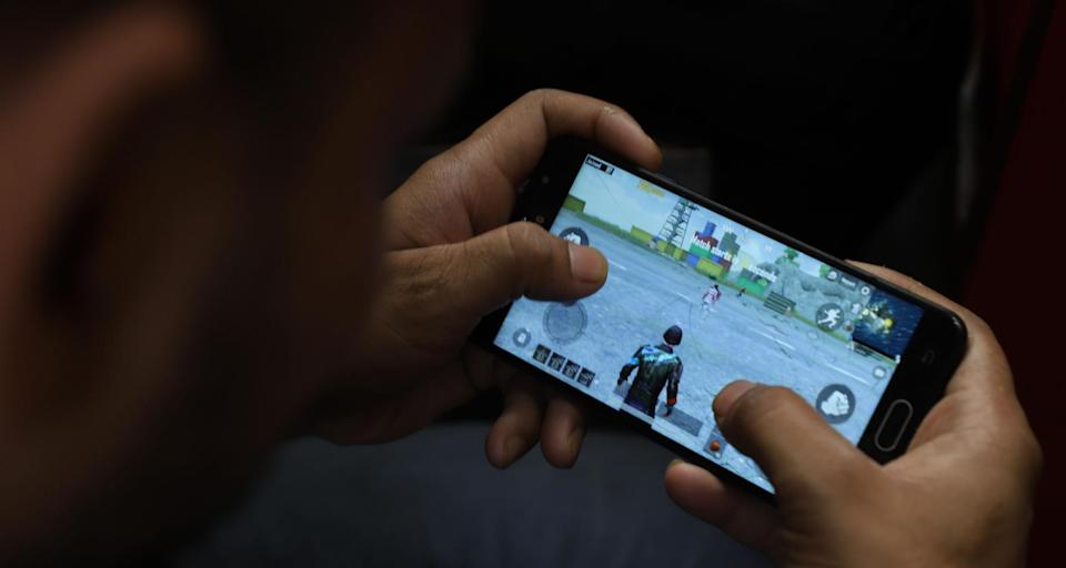A young boy plays PUBG on his mobile phone at a restaurant in New Delhi on May 3, 2019 (Photo by Nasir Kachroo/NurPhoto via Getty Images)