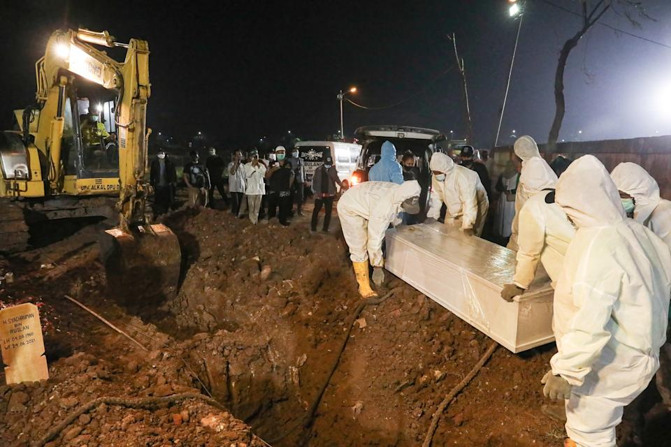 Wearing personal protective equipment funeral officers burry a covid 19 victim at the Rorotan Public Cemetery in Indonesia. Source: AAP