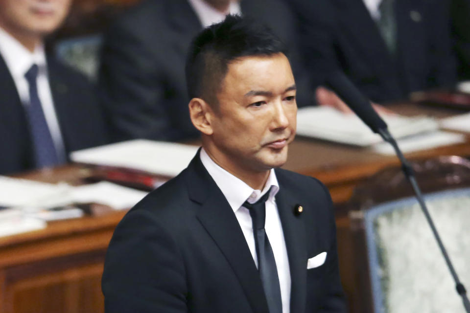 """FILE - In this Sept. 18, 2015, file photo, wearing a black tie, lawmaker Taro Yamamoto of Japan's opposition party """"Yamamoto Taro and his friends"""" prays with Buddhist prayer beads during a voting on a censure motion filed by Japan's major opposition Democratic Party of Japan against Prime Minister Shinzo Abe at the upper house plenary diet session in Tokyo. The billions being spent on the postponed Tokyo Olympics has entered the debate as Yuriko Koike opened the official campaign on Thursday, June 18, 2020 for reelection at the governor of Japan's capital. Yamamoto said the Olympics needed to be called off in a debate this week with Koike and other contenders. (AP Photo/Koji Sasahara, File)"""