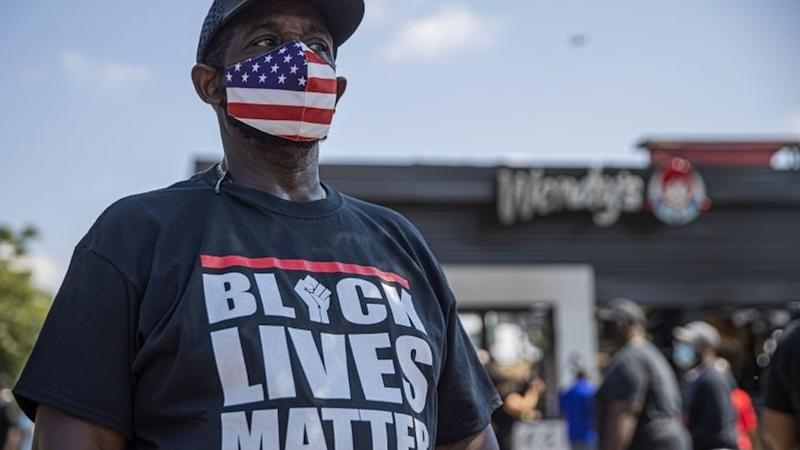A protester stands outside of a Wendy's restaurant that was set on fire after a black man was shot by a police officer on Friday 14 June 2020