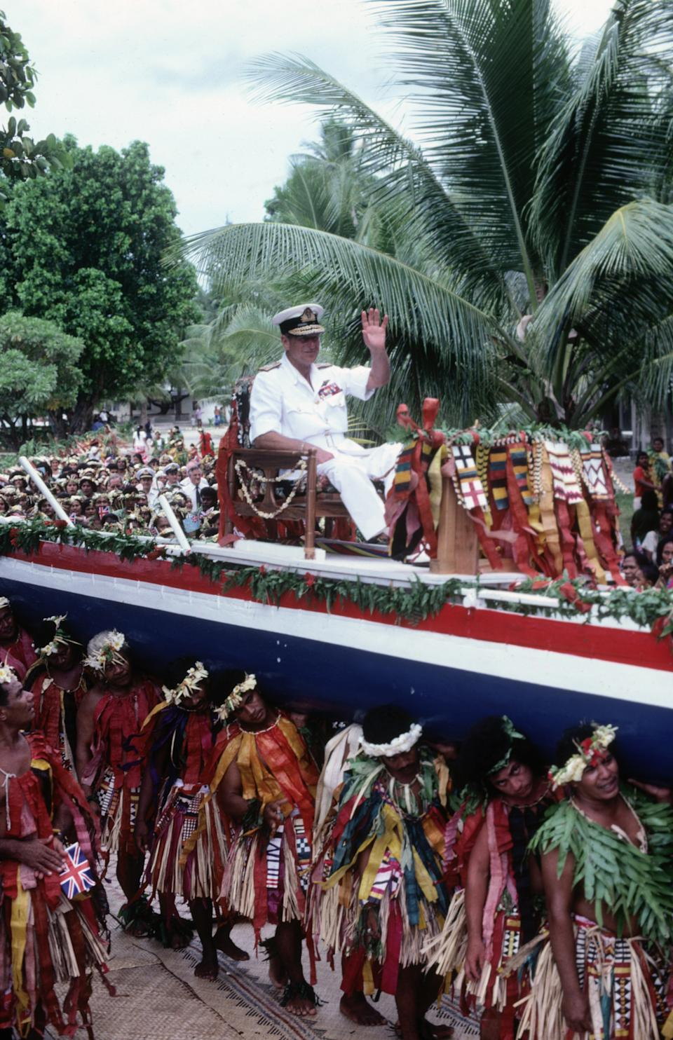 TUVALU - OCTOBER 26:  Prince Philip the Duke of Edinburgh is carried aloft on a canoe through the streets of the Pacific island of Tuvalu on October 26, 1982 during the Royal Tour of the South Pacific. (Photo by David Levenson/Getty Images)