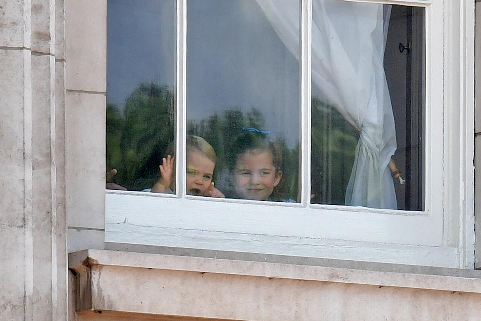 Prince Louis (L) and Princess Charlotte peer from a window in Buckingham Palace before a fly-past of aircraft by the Royal Air Force, in London on June 8, 2019. - The ceremony of Trooping the Colour is believed to have first been performed during the reign of King Charles II. Since 1748, the Trooping of the Colour has marked the official birthday of the British Sovereign. Over 1400 parading soldiers, almost 300 horses and 400 musicians take part in the event. (Photo by Daniel LEAL-OLIVAS / AFP) / The erroneous mention[s] appearing in the metadata of this photo by Daniel LEAL-OLIVAS has been modified in AFP systems in the following manner: [Louis] instead of [George]. Please immediately remove the erroneous mention[s] from all your online services and delete it (them) from your servers. If you have been authorized by AFP to distribute it (them) to third parties, please ensure that the same actions are carried out by them. Failure to promptly comply with these instructions will entail liability on your part for any continued or post notification usage. Therefore we thank you very much for all your attention and prompt action. We are sorry for the inconvenience this notification may cause and remain at your disposal for any further information you may require.        (Photo credit should read DANIEL LEAL-OLIVAS/AFP via Getty Images)