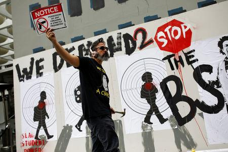 Manuel Oliver, father of Joaquin Oliver one of the victims of the mass shooting at Marjory Stoneman Douglas High School, holds up a placard as he paints a mural to commemorate the victims of the shooting and promote gun control in Los Angeles, California, U.S., April 7, 2018. REUTERS/Carlos Garcia Rawlins