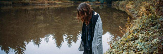 woman standing by a lake, looking down