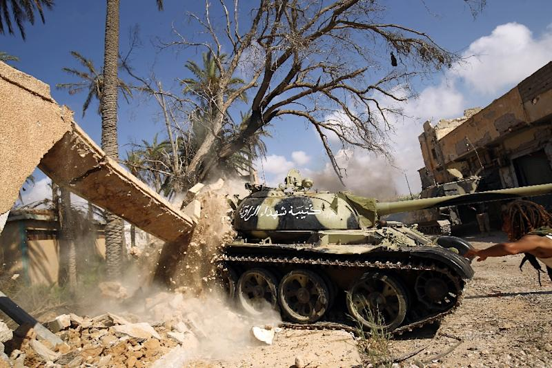Members of the self-styled Libyan National Army, loyal to the country's strongman Khalifa Haftar, roll a tank over a damaged building in central Benghazi on July 6, 2017