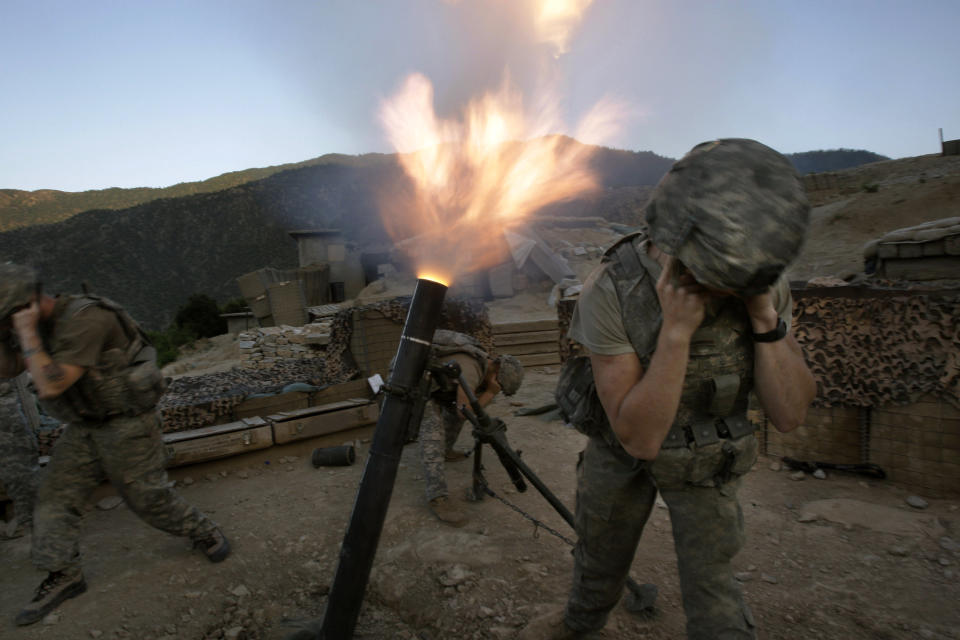 Soldiers from the U.S. Army First Battalion, 26th Infantry fire mortars from the Korengal Outpost at Taliban positions in the Korengal Valley of Afghanistan's Kunar Province on May 12, 2009. (AP Photo/David Guttenfelder, File)