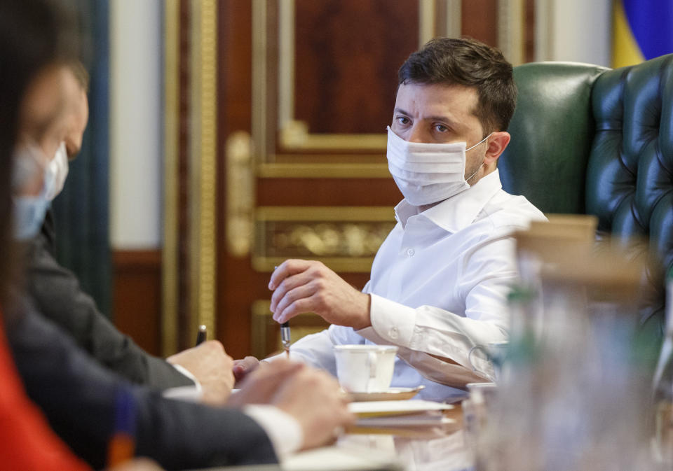 FILE - In this photo taken on Wednesday April 22, 2020, Ukrainian President Volodymyr Zelenskiy in a face mask to protect against coronavirus, discusses the COVID-19 situation in the country with officials in his office in Kyiv, Ukraine. Zelenskiy has switched to a special work mode as his wife Olena was tested positive for the coronavirus, his office said. (Ukrainian Presidential Press Office via AP)