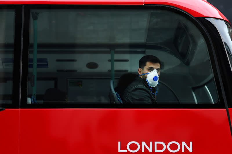 A man wears a mask while sitting on a bus in London