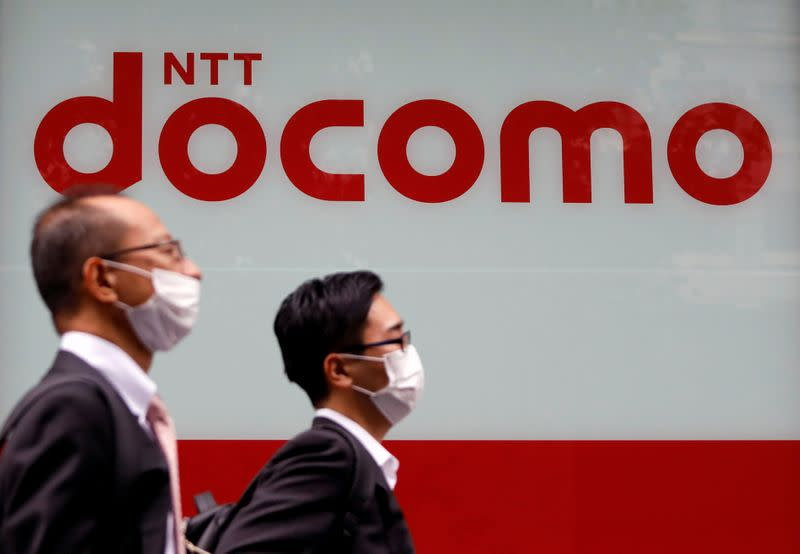 Passersby wearing protective face masks walk past in front of NTT Docomo shop in Tokyo, Japan