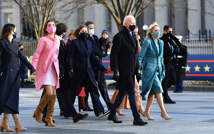 Joe Biden leads his family along the parade route in DC - GETTY IMAGES