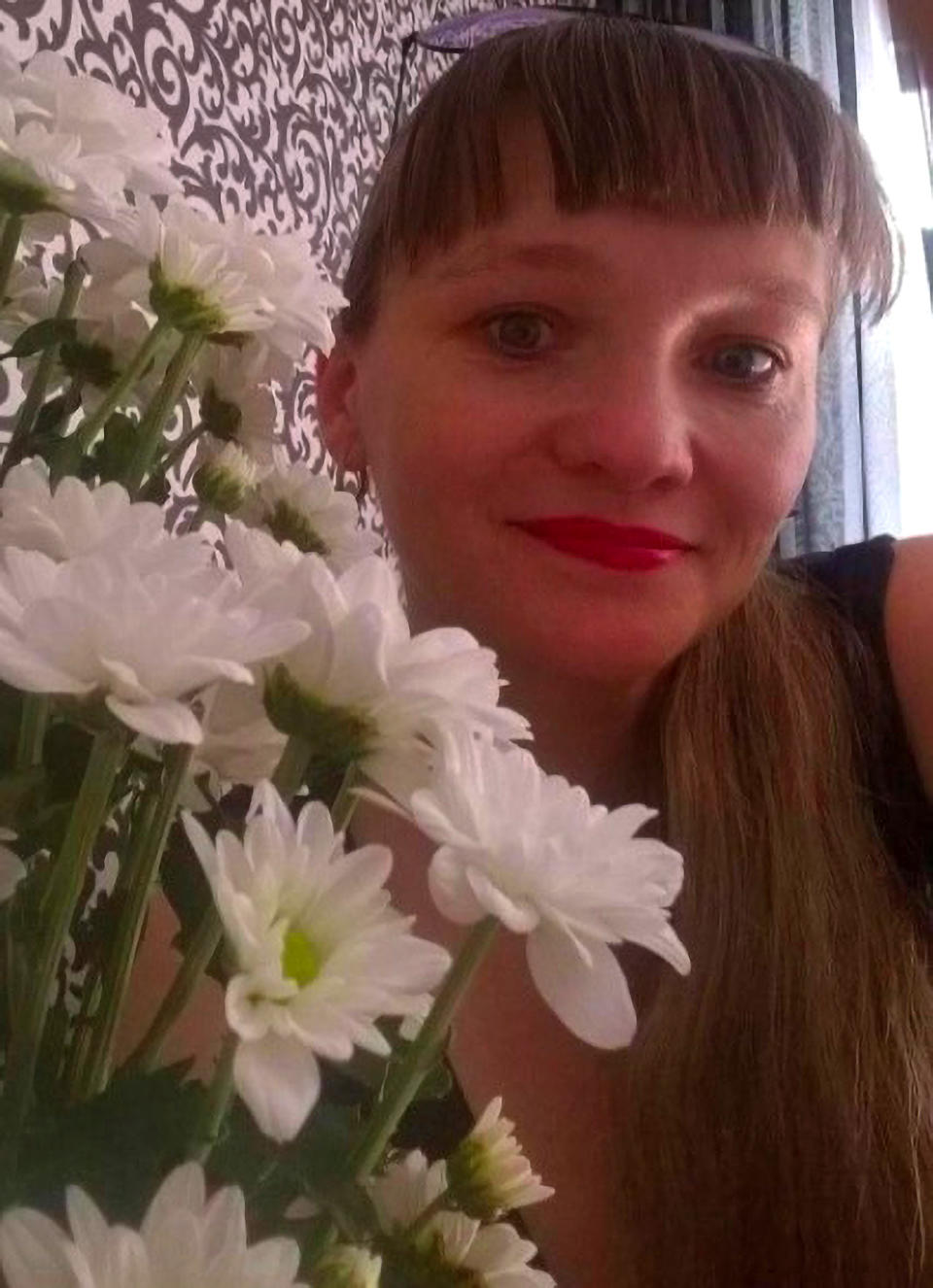Yulia Zykova is pictured with a bouquet of flowers. She is accused of keeping her unwanted baby in a closet.