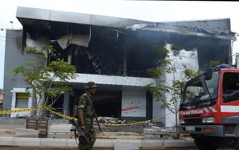 A Sri Lankan soldier stands guard after a fire at a Muslim-owned clothing store in Panadura on June 21, 2014